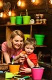 расти принципиальной схемы Маленький ребенок и мать брызгая молодой завод растя в баке Расти горшечного растения Активный сезон в стоковые фото