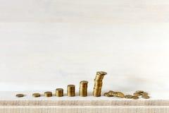 Растущие столбцы монеток, самое большое одно падают, все на деревянной предпосылке Не держите все ваши яичка в одной корзине Стоковая Фотография RF