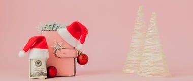 Расходы рождества Розовое кожаное портмоне с крышкой Санта Клауса, подарком, елью и долларами банкнот на розовой предпосылке Рожд стоковое фото