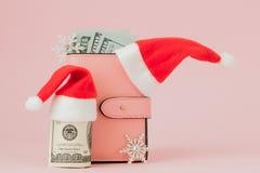 Расходы рождества Розовое кожаное портмоне с крышкой Санта Клауса, подарком, елью и долларами банкнот на розовой предпосылке Рожд стоковое изображение