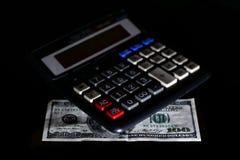 Расходы стоили, бюджет и налог или вычисление вклада, 100 долларов с калькулятором на темной черной таблице предпосылки стоковые фотографии rf