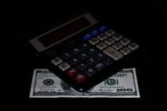 Расходы стоили, бюджет и налог или вычисление вклада, 100 долларов с калькулятором на темной черной таблице предпосылки стоковая фотография rf