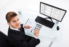 Расходы бизнесмена расчетливые на столе офиса Стоковое Изображение RF