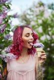 Расцветка волос макияжа в ярких красных, розовых волосах девушки с цветками сирени Яркий насыщенный цвет волос Женщина представля стоковые изображения