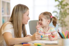 Расцветка девушки маленького ребенка с ручкой войлока рядом с ее матерью в живущей комнате Стоковая Фотография