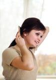 расчесывает детенышей волос девушки Стоковое Изображение