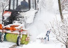 Расчистка снега Трактор освобождает дорогу, путь после сильного снегопада Трактор очищая дорогу от снега Экскаватор очищает улицу стоковая фотография