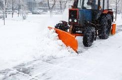 Расчистка снега Трактор освобождает дорогу, путь после сильного снегопада Трактор очищая дорогу от снега Экскаватор очищает улицу стоковое изображение rf