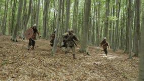 Ратники Викингов бегут в лесе на сражении видеоматериал