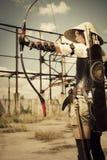 Ратник женщины держа в ее луке и стрелы рук и arhering Стоковые Изображения RF