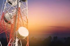 Радиосвязи возвышаются и сеть телекоммуникаций спутниковой антенна-тарелки с силуэтом области сельской местности в восходе солнца Стоковые Изображения