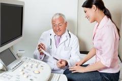 Радиолог показывая печать ультразвука к пациенту стоковое фото