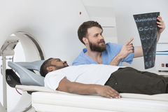 Радиолог показывая рентгеновский снимок к пациенту лежа на блоке развертки CT Стоковое фото RF