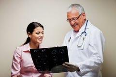 Радиолог показывая рентгеновский снимок к пациенту стоковые фото