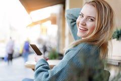 Радостная белокурая девушка наслаждаясь релаксацией с телефоном Стоковое фото RF
