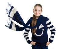 Радостная девушка в свитере и шарфе представляя в студии Летание шарфа в ветре стоковая фотография
