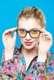 Радостная девушка в Eyeglasses представляет в студии смотря камеру Портрет смешной белокурой женщины с Ponytail Стоковые Фото