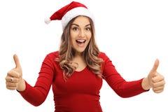 Радостная женщина нося шляпу рождества давая 2 большого пальца руки вверх Стоковое фото RF