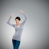 Радостная милая женщина кладет ее руки вверх при 2 пальца указанного вверх Стоковое Изображение