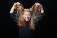 Радостная молодая белокурая женщина играет с ее волосами Стоковые Изображения