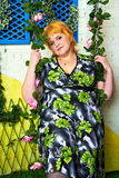 Радостная молодая женщина солнечного дня с золотым en на качании entwined с розовыми цветками в ярком платье на предпосылке окон c стоковые фото