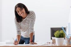 Радостная положительная женщина работая на проекте Стоковое фото RF