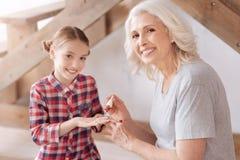 Радостная славная женщина крася ее ногти внучек стоковое фото