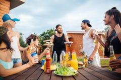 Радостное молодые люди есть и выпивая на таблице outdoors Стоковая Фотография RF
