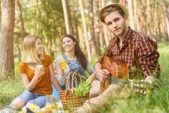 Радостное молодые люди ослабляя в лесе Стоковые Изображения