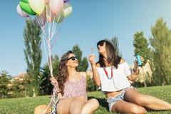 Радостные девушки имея потеху в парке Стоковая Фотография