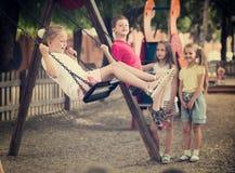 Радостные девушки и мальчики отбрасывая на спортивной площадке Стоковые Фотографии RF