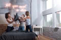 Радостные девушки стоя на кровати и имея бой подушками Стоковое Изображение