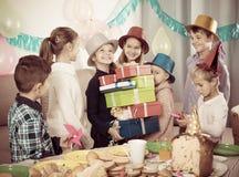 Радостные дети давая настоящие моменты к девушке во время партии Стоковые Фото
