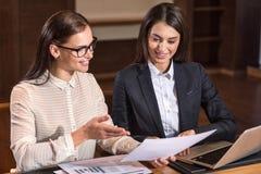 Радостные женские коллеги обсуждая проект в офисе Стоковое Изображение