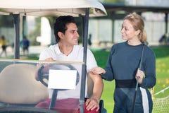 Радостные игроки в гольф человека и женщины ехать тележка гольфа Стоковое фото RF