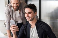 Радостные коллеги офиса используя телефон Стоковая Фотография RF