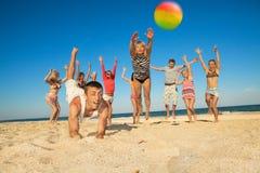 радостные люди играя волейбол Стоковые Фото