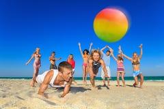 радостные люди играя волейбол Стоковое Изображение RF