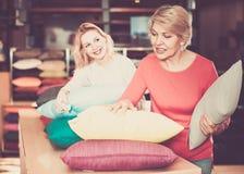 Радостные молодые и старшие женские клиенты смотря до подушки i стоковые фото