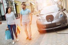 Радостные пары идя вниз с улицы после ходить по магазинам Стоковая Фотография
