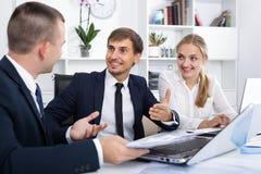 Радостные сотрудники имея переговор стоковые фото