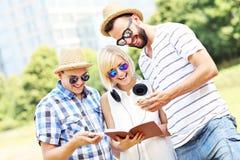 Радостные студенты изучая в парке Стоковые Изображения