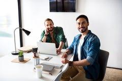 Радостные усмехаясь коллеги сидя в офисе Стоковые Фото