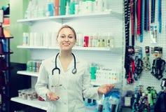Радостный ветеринар женщины рекомендуя на товарах для любимчиков Стоковые Фотографии RF
