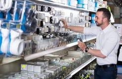 Радостный выбирать человека электрический затыкает внутри магазин домочадца стоковые изображения