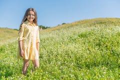 Радостный женский ребенк имея потеху на поле лета Стоковые Фото