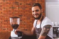 Радостный мужской бармен работая в кофейне стоковая фотография