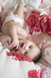 Радостный младенец лежа в кровати на его назад Стоковые Изображения RF
