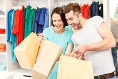 Радостный парень и подруга покупая в бутике Стоковое Изображение