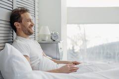 Радостный парень ослабляя в спальне Стоковые Фото